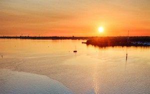 Sailing boats on lake Gooimeer during sunset