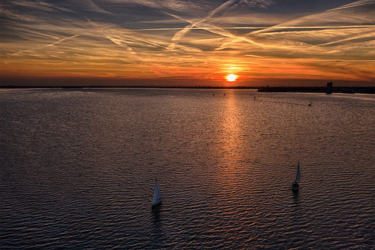 Sailing boats on Gooimeer during sunset