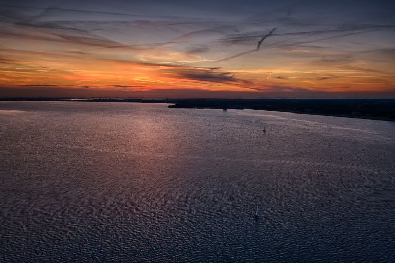 Lonely sailing boats on lake Gooimeer during sunset