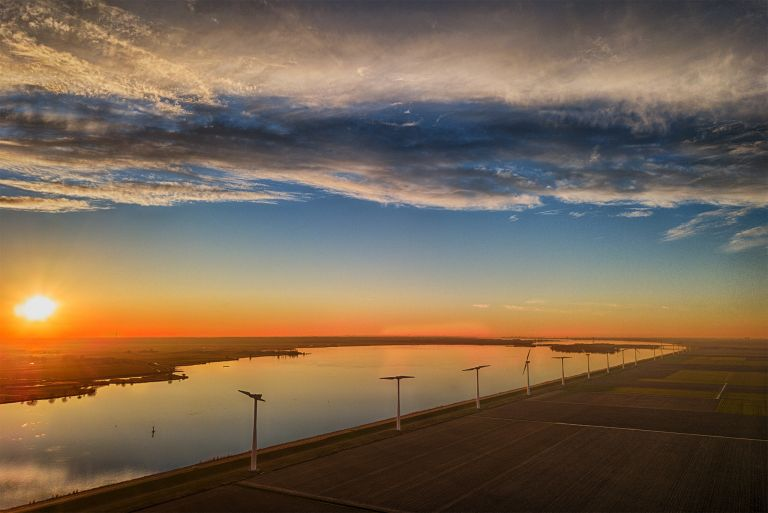 Fields, windmill and lake Eemmeer from my drone during sunset