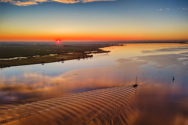 Sunset drone picture of lake Eemmeer, as a boat passes