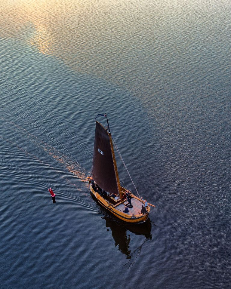 Sailing boat on lake Gooimeer during sunset