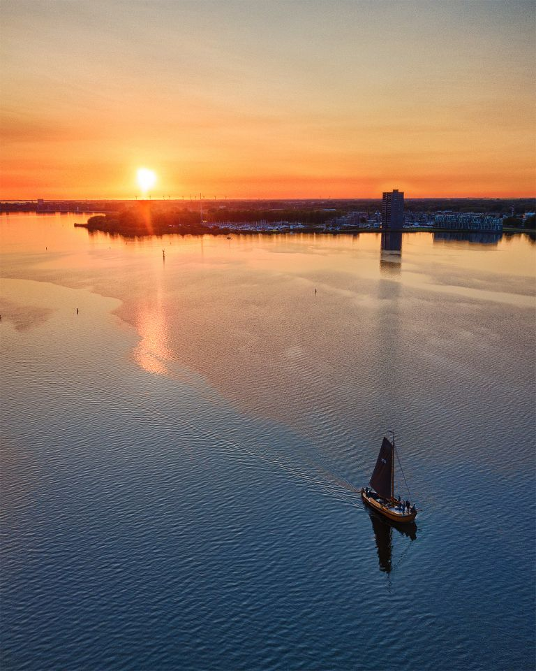 Sailing boat on lake Gooimeer during sunset