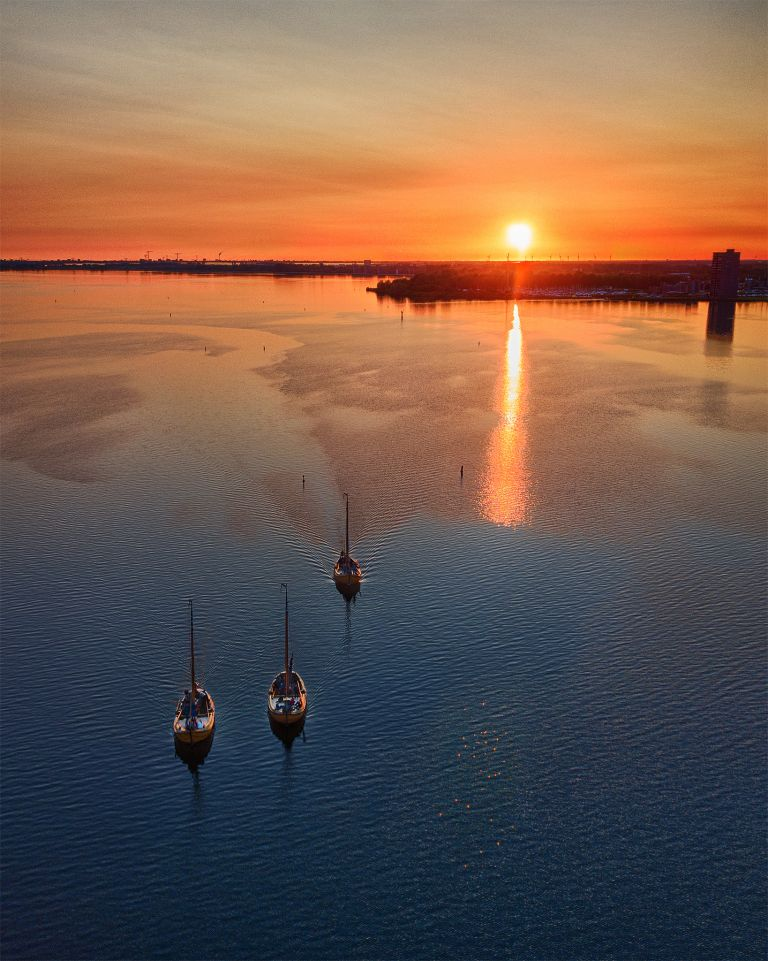 Sailing boats on lake Gooimeer during sunset