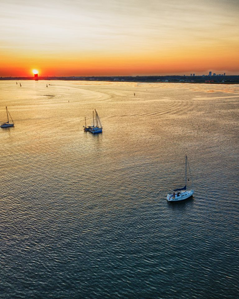 Boats on lake Gooimeer during sunset