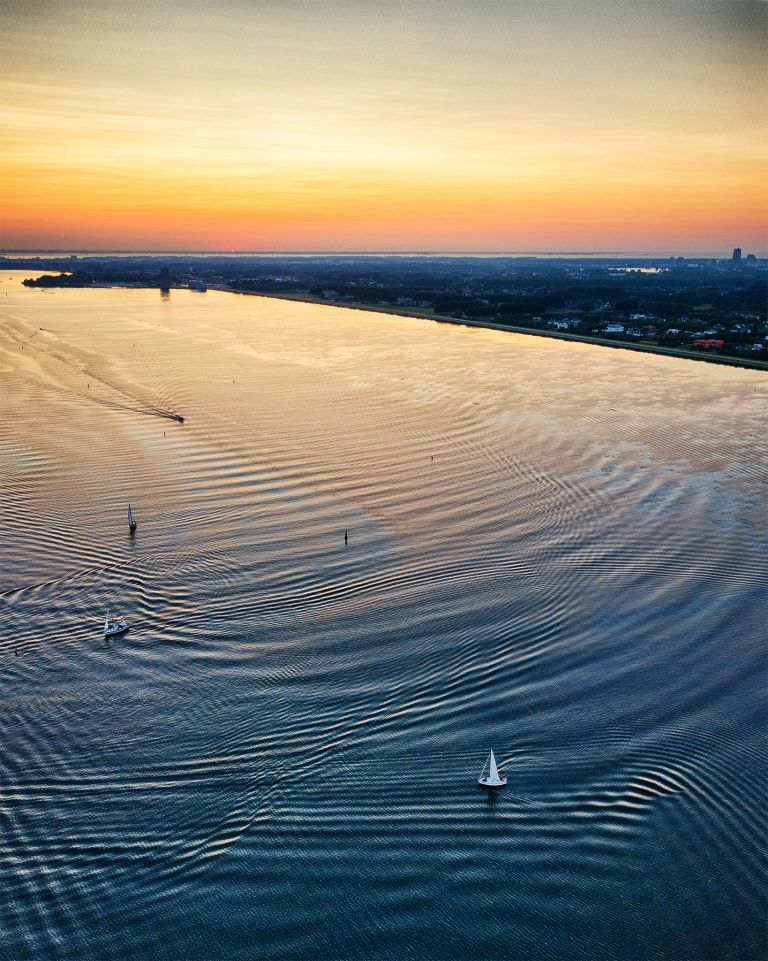 Boats sailing on lake Gooimeer during sunset