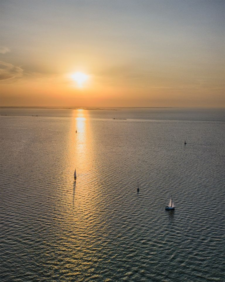 Boats sailing on lake Markermeer during sunset
